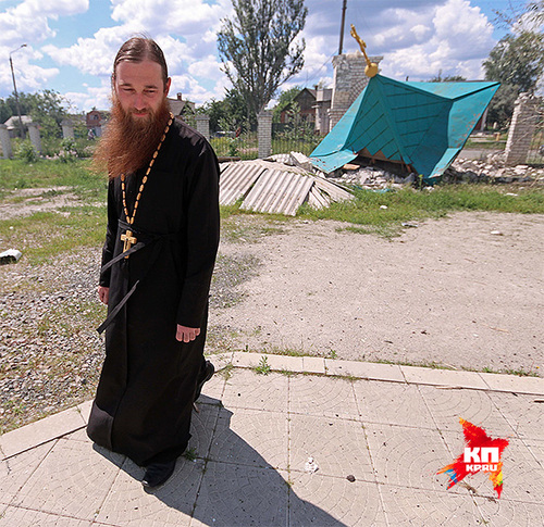 Отец Алексей на фоне уничтоженной бомбежками часовенки православного храма под Славянском